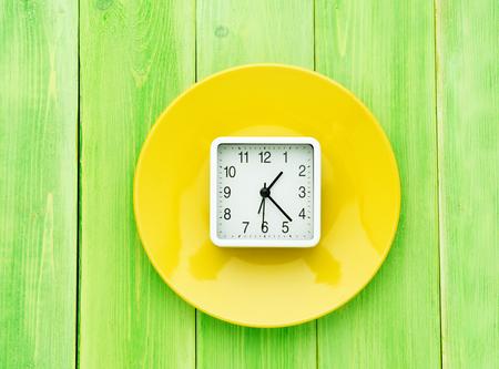 Reloj en placa de color amarillo brillante sobre fondo de madera verde brillante, vista superior Foto de archivo