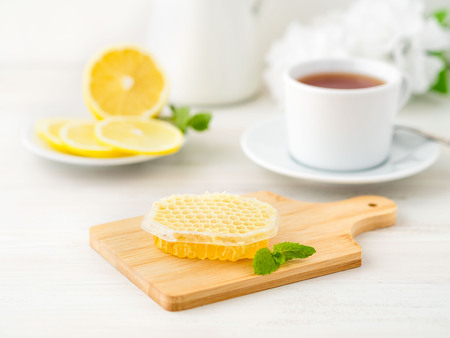 White Cup of tea, honey, honeycomb, lemon on a white background. Folk method of treating colds. Side view, selective focus
