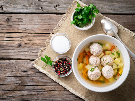 soup with meatballs in a white plate on an old wooden rustic grey table, top view