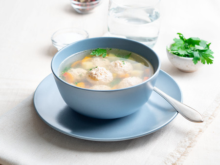 soup with meatballs in a blue plate, white linen tablecloth and napkins, light background, side view