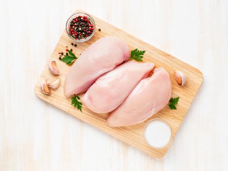 Filet de poulet cru aux épices sur une planche de bois sur une table en bois blanc, vue du dessus