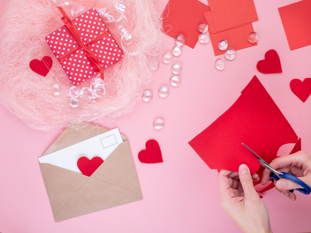 woman cuts out red felt hearts, homemade crafts for Valentine's day, hand made creativity, top view. Stockfoto