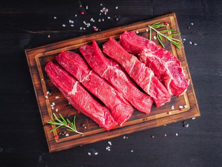 Raw meat, beef steak with seasoning on chopping board on dark background with rosemary, seasonings, top view.