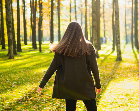 Girl with long dark hair is spinning in Park in sunlight. Woman stands with her back, facing sun, looking forward.