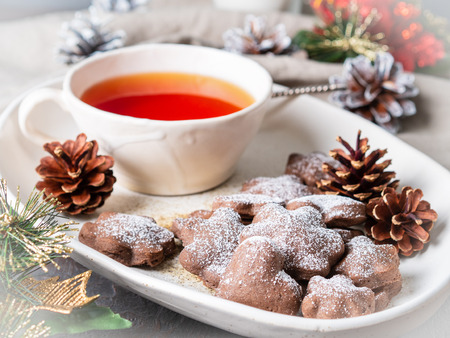 Christmas or new year card. Winter holiday composition, side view, selective focus, blue, gray background. Cup of tea, cookies, fir cones, candles, gift 免版税图像