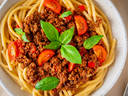 pasta bolognese with tomato sauce, ground minced beef, basil leaves on white table, linen napkin, top view, close-up