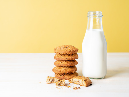 Oatmeal cookies with flax seeds and milk in bottle, healthy snack. Light background, bright yellow wall. Stock Photo