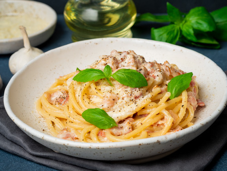 Carbonara pasta, spaghetti with pancetta, egg, parmesan cheese and cream sauce. Traditional italian cuisine. Side view, close up. Stock Photo