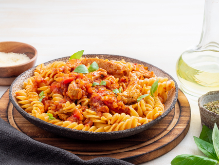 fusilli pasta with tomato sauce, chicken fillet with basil leaves on light white wooden background, side view. Banque d'images