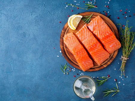 Food background, sliced portions large salmon fillet steaks on chopping board on dark blue concrete table, copy space, top view. Stock Photo