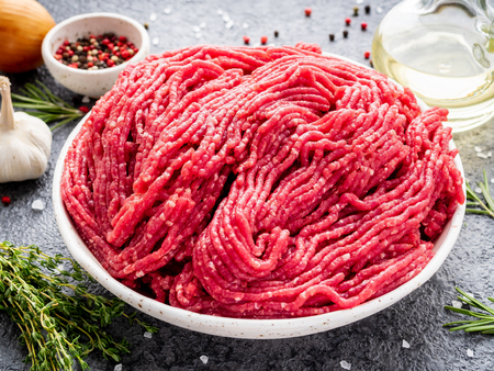 Mince beef, ground meat with ingredients for cooking on dark gray background, side view, close up. Banque d'images - 113442902