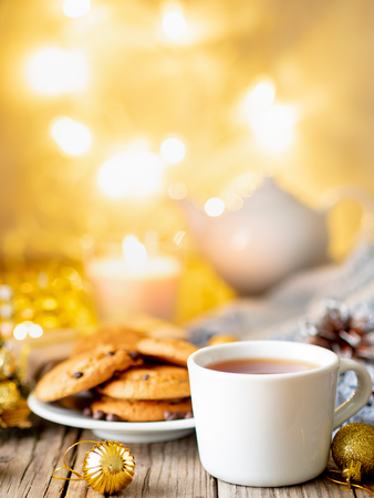 Christmas background with Chocolate chip cookies, cup of tea. Cozy evening, mug of drink, Christmas decorations, candles and lights garlands.