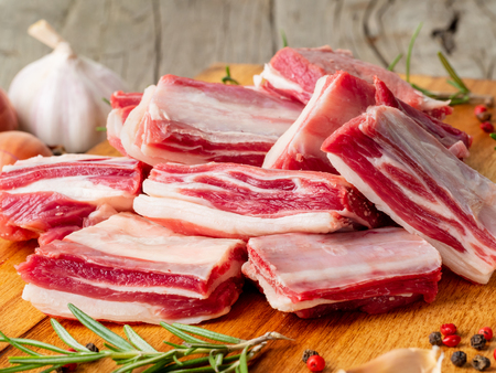 Small pieces of raw lamb ribs on wooden chopping Board on old rustic wooden background, side view Archivio Fotografico