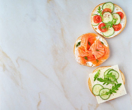 three delicious open sandwiches with salmon, tomatoes, cucumber and cheese on light marble table, copy space
