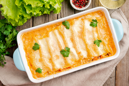 Cannelloni with filling of ground beef, tomatoes, baked with bechamel tomato sauce, top view, old dark wooden background Stockfoto