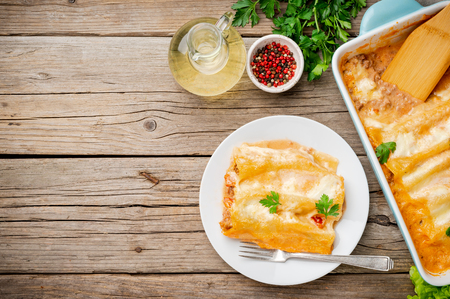 Cannelloni with filling of ground beef, tomatoes, baked with bechamel tomato sauce, top view, old dark wooden background, copy space