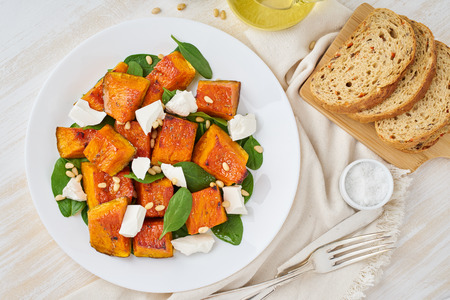 Salad with roasted pumpkin, feta cheese, spinach, nuts with honey and seasonings, top view Stock Photo