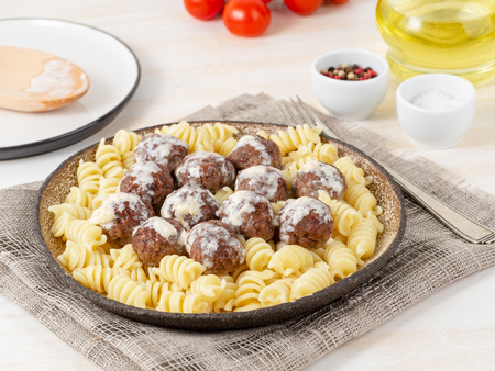 Swedish meatballs with sauce and fusilli paste on white wooden table, side view. Imagens