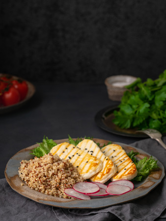 Halloumi, grilled cheese with quinoa, salad, radish. Balanced diet on  dark background, copy space