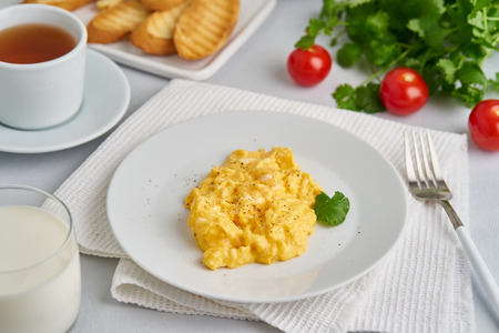 Scrambled eggs, omelet, side view. Breakfast with pan-fried eggs, glass of milk, tomatoes on white background. 版權商用圖片