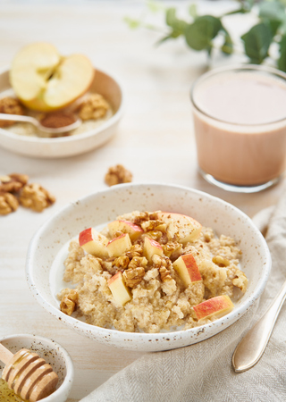 Oatmeal with apple, nuts, cinnamon, honey and cup of cocoa on white wooden light background. Vertical. Healthy diet breakfast
