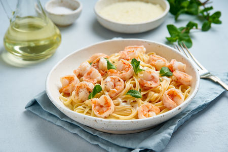 Pasta spaghetti with grilled shrimps, bechamel sauce, mint leaf on blue table, italian cuisine, side view Banque d'images