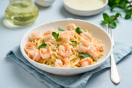 Pasta spaghetti with fried shrimps, bechamel sauce, mint leaf on blue table, italian cuisine, side view Banque d'images