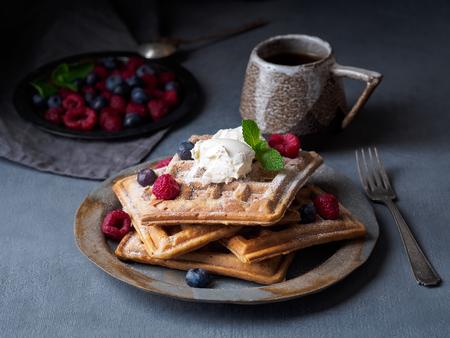 Belgian waffles with raspberries, chocolate syrup. Breakfast with tea on dark background, side view Reklamní fotografie