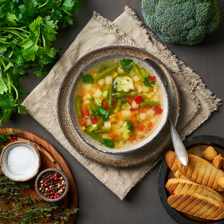 Vegetable soup, dietary vegetarian bright spring dish, linen napkin, top view, brown dark background. Stok Fotoğraf