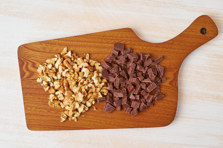 Chopped walnuts and chocolate on a wooden board. Step by step recipe  for Banana bread.