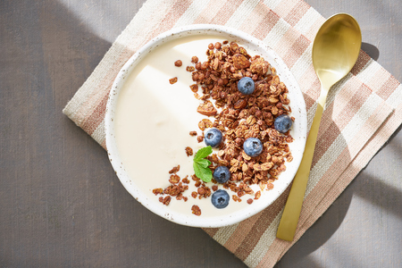 Yogurt with chocolate granola, bilberry. Breakfast on brown table, top view, sun light