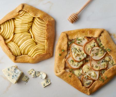 Galette di frutta, torta di mele con miele, torta salata di pere e formaggio, tavolo in marmo, vista dall'alto Archivio Fotografico
