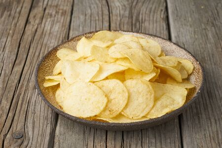 crisp in bowl, wooden background, closeup