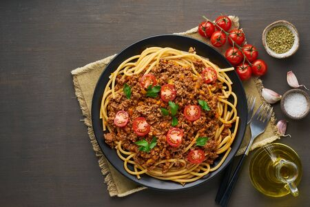 mediterranean pasta bolognese bucatini with mincemeat, tomatoes, carrot and basil leaves Standard-Bild