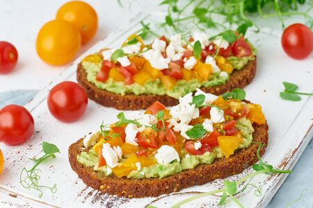 avocado toast with feta and tomatoes, smorrebrod with ricotta, closeup