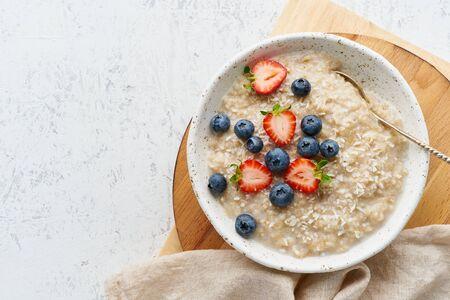 Porridge rustico della farina d'avena con il mirtillo, il mirtillo, la mora, la fragola, la dieta del precipitare, fondo bianco di legno, spazio della copia di vista superiore