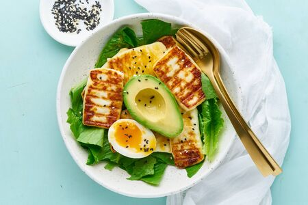 ketogenic diet soft boiled eggs with grilled haloumi, avocado and lettuce, mediterranean cuisine on pastel background 스톡 콘텐츠