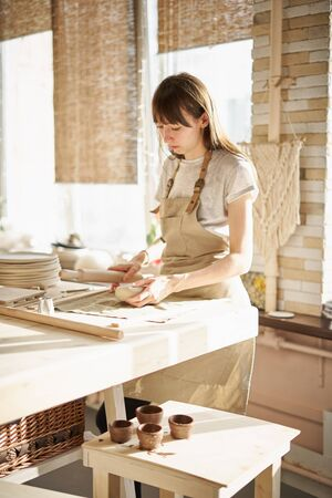 Beautiful young woman making ceramic ware, roll out with a rolling pin in sun light. Concept for woman in freelance, business, hobby