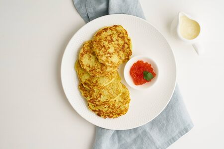 Balanced and gluten free zucchini pancakes with red caviar and sause