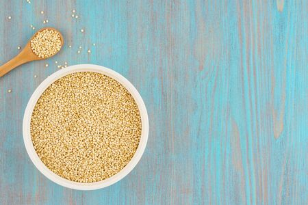 quinoa seed grain in white bowl with spoon on wooden blue table , top view, copy space 스톡 콘텐츠