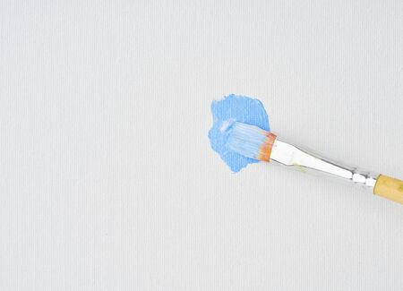 Brush draws blue paint on canvas, close up. Action painting art. Artist began to paint picture, first brushstrokes, copy space Archivio Fotografico