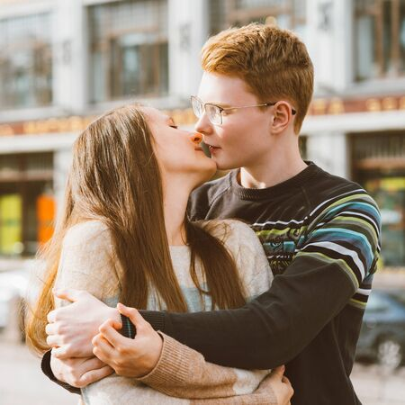 The redhead boy looks tenderly at girl and kiss. Concept of teenage love and first kiss, love, relationship, couple. City, waterfront.