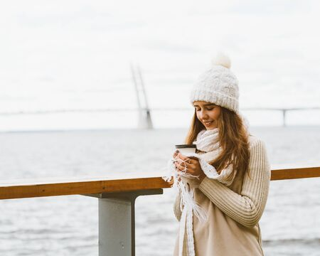 Beautiful young girl drinking coffee, tea from plastic mug in autumn, winter. A woman with long hair stands on waterfront on Baltic sea in port and waiting for ferry, heated by a hot drink, copy space
