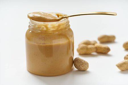 jar of peanut butter and peanuts in a shell on a white table, side view, fresh ground crushed nuts, side view