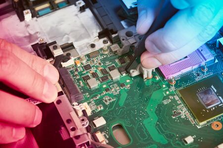Man repairs computer. A service engineer in a shirt repairs a laptop, at a white Desk against a white wall. Computer motherboard background with blur neon multicolor glow. Hands close up.