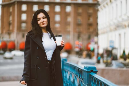 Beautiful serious smart brunette girl holding cup of coffee in hands goes walking down street in a enter on blue bridge. Charming thoughtful woman with long hair wanders alone, immersed in thoughts