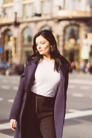 Portrait f beautiful intelligent brunette who walks down street of Saint-Petersburg in city center. Charming thoughtful woman with a long dark hair wanders alone, immersed in thoughts, copy space