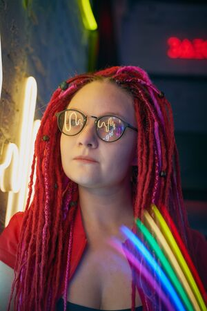 Girl in neon lights at party in nightclub, beautiful woman in sunglasses, with long pink hair, with dreadlocks pigtails, bright and stylish in the glow of neon signs, vertical, close up Standard-Bild - 133236211