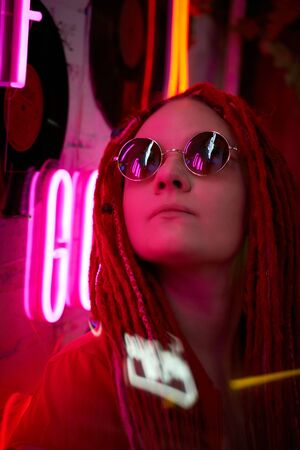 Girl in neon lights at party in nightclub, beautiful woman in sunglasses, with long pink hair, with dreadlocks pigtails, bright and stylish in the glow of neon signs, vertical Standard-Bild - 133236213