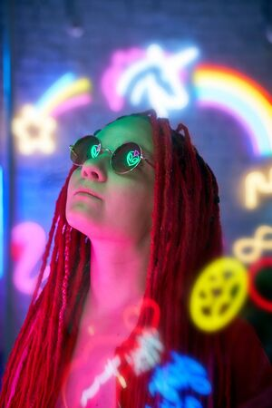 Girl in neon lights at party in nightclub, beautiful woman in sunglasses, with long pink hair, with dreadlocks pigtails, bright and stylish in the glow of neon signs, vertical, close up Standard-Bild - 133236215